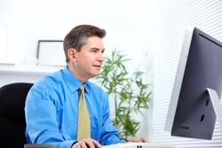 Man in light blue shirt and tie working on desktop computer
